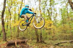 A young guy in a helmet flies landed on a bicycle after jumping from a kicker Stock Image