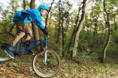 A young guy in a helmet flies landed on a bicycle after jumping from a kicker. A young rider in a helmet and a blue sweatshirt flies on a bicycle after jumping Stock Photo