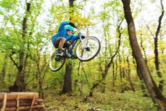 A young guy in a helmet flies landed on a bicycle after jumping from a kicker. A young rider in a helmet and a blue sweatshirt flies on a bicycle after jumping Stock Image