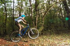 A young guy in a helmet flies landed on a bicycle after jumping from a kicker. A young rider in a helmet flies landed on a bicycle after jumping from a high Royalty Free Stock Photography