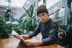 Young guy in hipster glasses and hat reading an interesting book in a nice cafe where a lot of green. Young and handsome guy in hipster glasses and hat reading Stock Photography