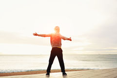 A young guy with his arms outstretched at the seaside standing next to the sea Royalty Free Stock Image