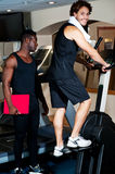 Young guy with his personal trainer beside him Royalty Free Stock Image