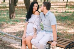 A young guy and his pregnant girl are sitting on a bench, against the background of greenery and trees. In anticipation of a child. First pregnancy I love stock photo