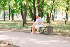 A young guy and his pregnant girl are sitting on a bench, against the background of greenery and trees. In anticipation of a child. First pregnancy I love stock photos