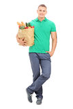 Young guy holding a bag full of groceries Royalty Free Stock Photography