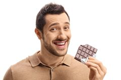 Young guy holding a bitten chocolate bar and smiling. Isolated on white background Royalty Free Stock Photos