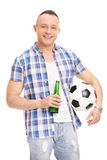Young guy holding a bottle of beer and football Royalty Free Stock Images