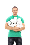 Young guy holding a bunch of toilet paper rolls Royalty Free Stock Photo