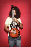 Young guy holding an electric guitar beautiful long curly hair Royalty Free Stock Photos
