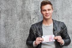 Young guy holding 10 euro Royalty Free Stock Photography