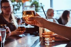 Young man holding a glass of beer sitting in a caf with his friends. Young guy holding a glass of beer sitting in a caf with his friends stock photography
