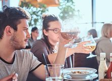 Young man holding a glass of beer sitting in a caf with his friends. Young guy holding a glass of beer sitting in a caf with his friends royalty free stock images
