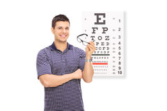 Young guy holding glasses in front of an eye chart Royalty Free Stock Photo