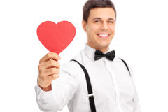 Young guy holding a heart shaped piece of cardboard Stock Photo