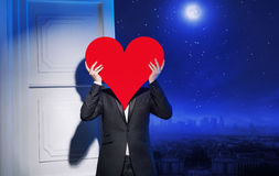 Young guy holding a heavy red heart Stock Photos