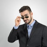 Young guy holding and looking over sunglasses. Royalty Free Stock Image