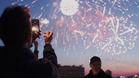 Young guy is holding a smartphone with sparklIng light and recording a video of fireworks on the rooftop. Friends stock footage