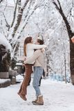 Young guy holds a beautiful girl in his arms. Couple in sweaters. stock photos