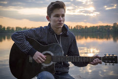 Young guy in a hood plays guitar on the bridge in the evening against the backdrop of a sunset on the river Royalty Free Stock Image
