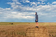A young guy in a hood stands on a haystack in a wheat field after a rain with a storm sky on the background royalty free stock images