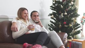 Young guy hugging his girlfriend sitting on a couch drinking coffee next to the Christmas tree. Love relationship. Young guy hugging his girlfriend sitting on a stock footage