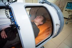 Young guy in a hyperbaric chamber, oxygen treatment. Medical chamber royalty free stock photos
