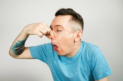Free Young Guy Inserts Two Fingers In The Mouth To Induce Vomiting, On A Light Background Stock Image - 167699161