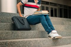Young guy in jeans sits on the steps and put near yourself black bag. Close-up Stock Photos