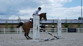 Young guy jump over the barrier on the horseback stock footage