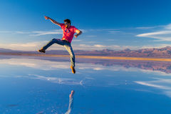 Young guy jumping on a exotic place in Atacama Desert, Chile Royalty Free Stock Image