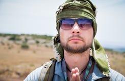 Young guy in keffiyeh making Namaste gesture. Royalty Free Stock Photo
