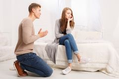 The guy asks the girl for forgiveness. A young guy kneels and asks for forgiveness from his girlfriend. The girl offended turned away from the guy royalty free stock photos