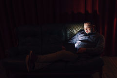Young guy with laptop watch movie on couch at home Stock Photo