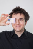 Young guy laughing with his driver license Stock Image