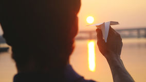 Young guy launch paper plane against the sea during sunset with sun flare and reflections in the water, as in childhood Royalty Free Stock Photo