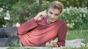 Young guy talks on phone and relax in park stock footage