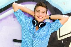 Young guy leaning on graffiti wall Stock Photo
