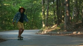 A young guy learns to ride a longboard. It is located in the forest. Dressed in a plaid shirt and a felt hat. Active