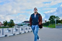 Young guy in leather jacket and jeans is coming down the street stock image