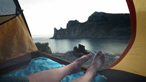 A young guy lies in a camp tent, his legs protrude from the tent. Enjoys relaxing on the beach after the adventure of