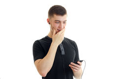 Young guy listens to music with headphones and closes the mouth hand Stock Photo