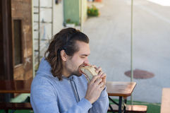 Young guy with long hair eats big sandwich Royalty Free Stock Photo