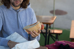 Young guy with long hair eats big sandwich Stock Image