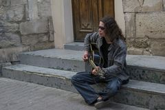 Young guy with long hair in sunglesses playing guitar on the street stock photo