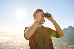 Young guy looking at the horizon with binoculars outdoors Stock Photography