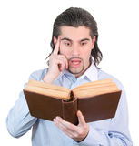 Young guy looks into book and thinks isolated. Young dark haired caucasian man in light blue shirt reads book and scratches his head in confusion isolated on Royalty Free Stock Photography
