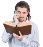 Young guy looks into book and thinks isolated. Young dark haired caucasian man in light blue shirt reads book and scratches his head in confusion isolated on Stock Images