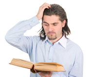 Young guy looks into book and understands nothing. Young dark haired caucasian man in light blue shirt reads book and scratches his head in confusion isolated on Stock Image