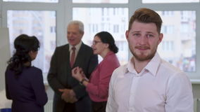 Young guy looks at business people. Young caucasian guy looking at business people at the office. Attractive bearded man standing against background of stock video